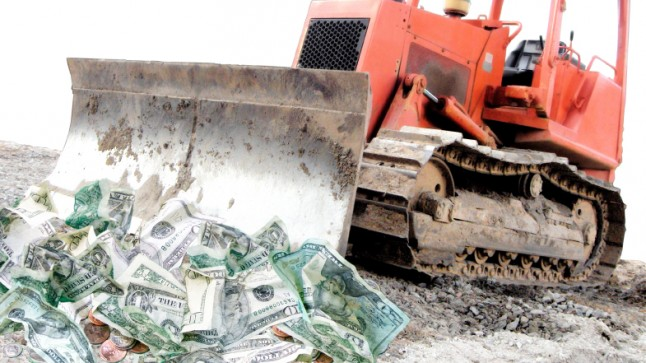 A bulldozer pushing piles of money